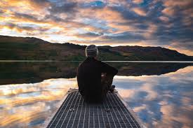 Man sitting on dock at lake with sunset