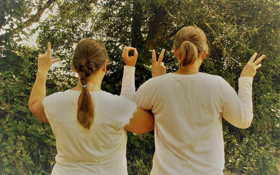 Two women facing away spelling out LOVE with their hands