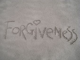 The word Forgiveness written in sand