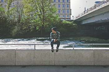 A boy sitting on a bridge railing thinking