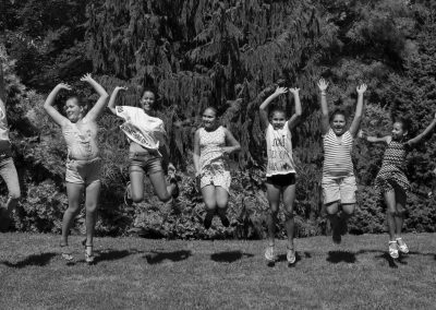 black and white photo of eight kids in a line in mid air from jumping