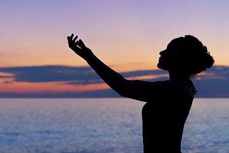 Silhouette of woman in front of water and sunset with arms up praying