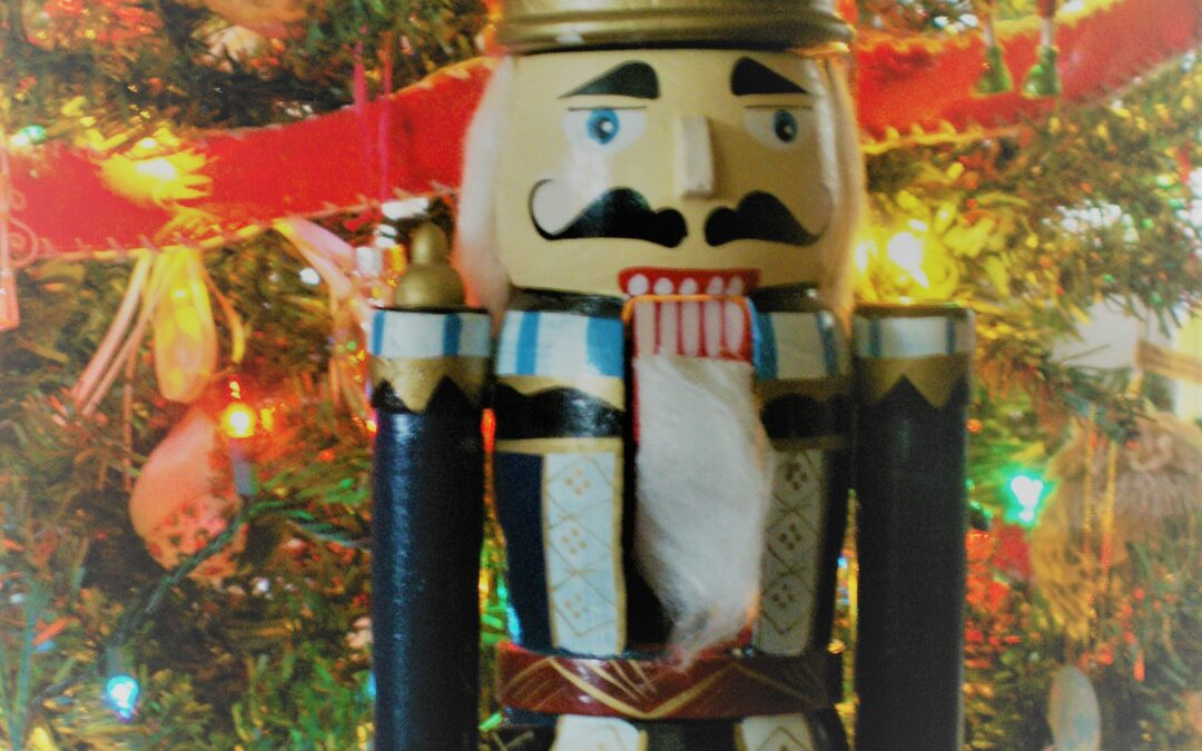 A Nutcracker in front of a Christmas tree